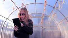 Girl in a Greenhouse With Tablet - stock footage