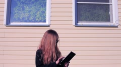 Girl on the Background of the House With Windows in Sunglasses With Tablet - stock footage