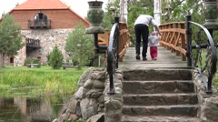 Father teach toddler kid to walk on wooden bridge over river in park. 4K Stock Footage