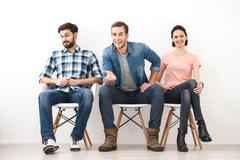 Skillful three workers are sitting with anticipation - stock photo