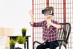 Girl getting experience using VR-headset glasses of virtual reality - stock photo