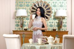 Beautiful brunette drinking tea in hotel room Stock Photos