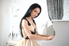 Charming brunette in evening dress playing the piano. Stock Photos