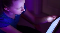 Young girl write text message very quickly on her tablet in a dark room  Stock Footage