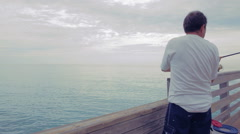 Mature Man Fishing Off of Pier At Ocean Stock Footage