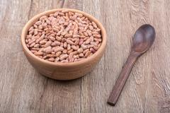 Bowl with beans and wooden spoon on a wooden background - stock photo