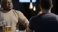Bartender having a lively conversation with a customer - stock footage