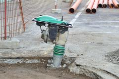 Gasoline or diesel vibratory plate compactor at road construction site - stock photo