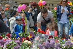 Laying flowers to Glory Monument in Victory Day, Dnepropetrovsk, Ukraine. - stock photo