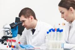 Cheerful young scientists are doing analysis in lab Stock Photos