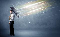 Business man defending light beams with umbrella concept - stock photo