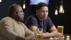 A man consoling his troubled friend at a bar - stock footage