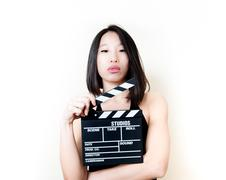 Young asian woman and movie clapper board Stock Photos