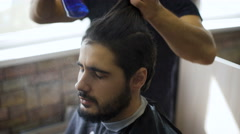 Getting groomed. Shot of a handsome bearded barber giving a haircut to his Stock Footage