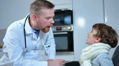 Home doctor came to sick boy and his mother. he examines a child and records Stock Footage