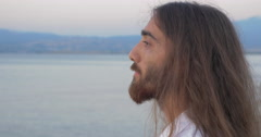 Long-haired man with beard looking to the camera - stock footage