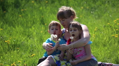 The mother with children blowing on a dandelion Stock Footage