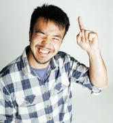 young cute asian man on white background gesturing emotional, pointing, smiling - stock photo