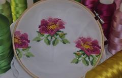 Embroidered cross flowers in wooden hoop Stock Photos
