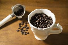 Coffee beans in an ornate coffee mug. - stock photo