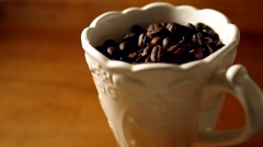 Coffee beans in an ornate mug Stock Footage