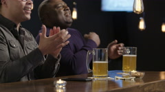 Two guys cheering for their team at a bar Stock Footage