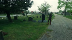 Girl Walks and Kneels Down at a Tombstone Stock Footage