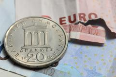 torn euro note and vintage greek coin - stock photo