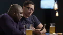 Two guys sharing a cell phone at a bar Stock Footage