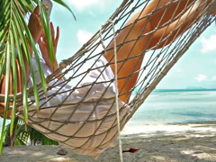 Young woman resting in a hammock with phone  on a tropical beach Stock Footage