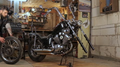 Biker collects in parts motorcycle in the garage Stock Footage