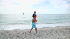 Grandpa Giving Grandson Ride On Shoulders At The Beach Stock Footage