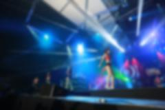 Crowd in front of concert stage with dancer blurred - stock photo