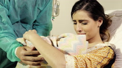 Woman in hospital receiving new born baby from husband in love - stock footage