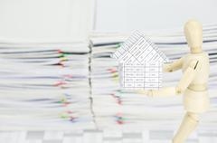 Wooden dummy holding house have blur overload paperwork as background Stock Photos