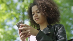 Beautiful young girl with dark curly hair using her cell phone, outdoor. - stock footage