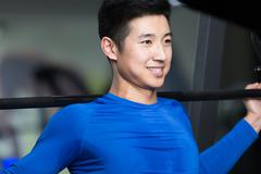 Young asian man working out in modern gym Stock Photos