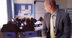 4K Portrait of smiling teacher in classroom with students working at their desks Stock Footage