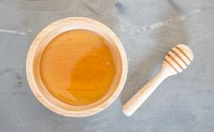 Golden honey cup and dipper on top view - stock photo