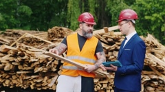 The engineer in a suit and a helmet with a bearded worker studying samples of Stock Footage