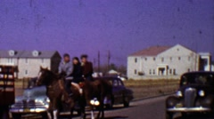 1955: Family crossing street riding horse as classic car drives by. Stock Footage
