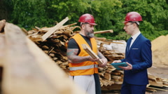 The inspector in a helmet and a suit with a builder studying samples of Stock Footage