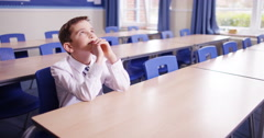 4K Happy little boy sitting on his own & daydreaming in school classroom Stock Footage