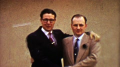 1955: Businessmen colleagues awkwardly embrace during winter snowstorm. Stock Footage