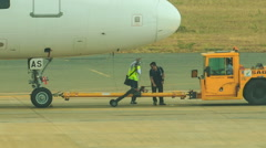 Tow Tractor Pushbacks Airliner along Airfield Workers Walk Near Stock Footage