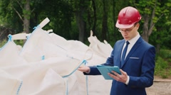 Engineer in helmet and suit holds product audits in large bags Stock Footage