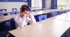 4K Unhappy little boy sitting alone in school classroom with worries on his mind Stock Footage