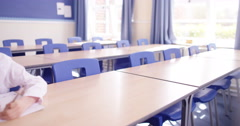 4K Little boy sitting alone to do his work in school classroom Stock Footage