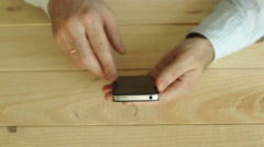 Smartphone in a male's hands on old light wooden background Stock Footage