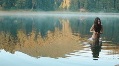 Young beautiful naked mermaid in the picturesque mountain lake surrounded by Stock Footage